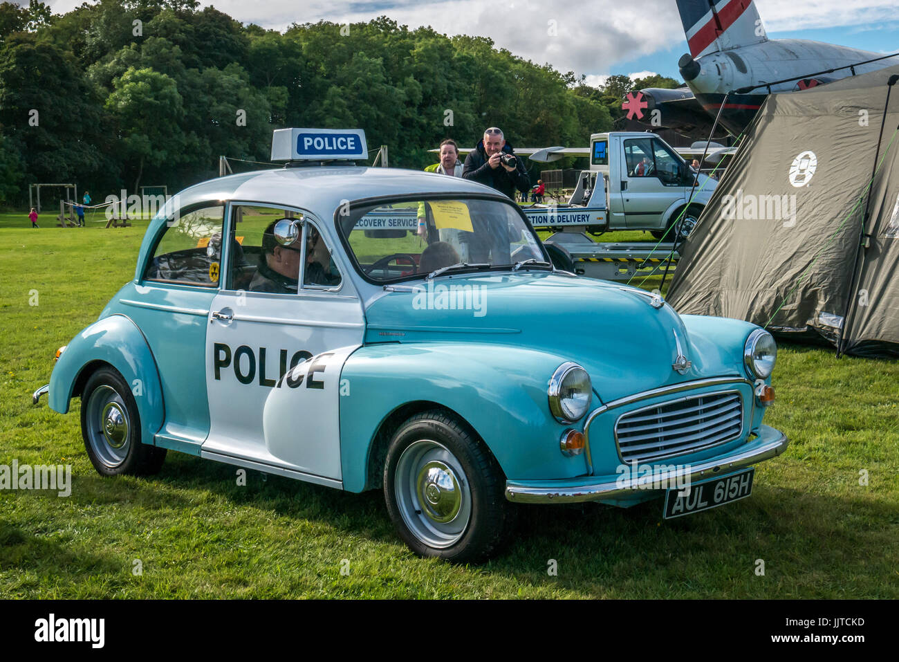 Man sitting in vintage Morris Minor police car, with couple taking a photo, Wheels and wings family day 2016, East Fortune, East Lothian, Scotland, UK Stock Photo