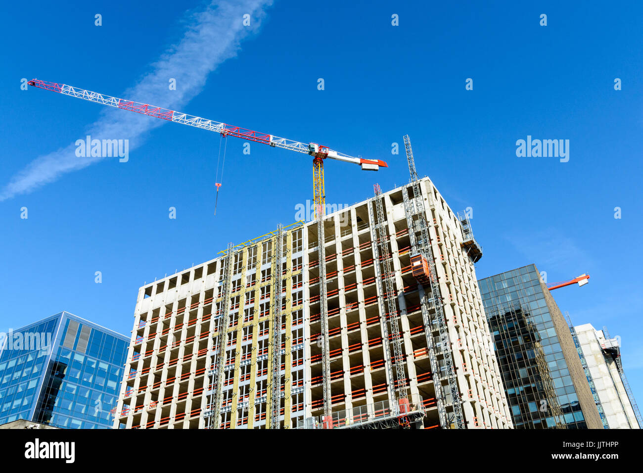 Low angle view of a concrete building under construction between glass buildings with a red and white tower crane Stock Photo