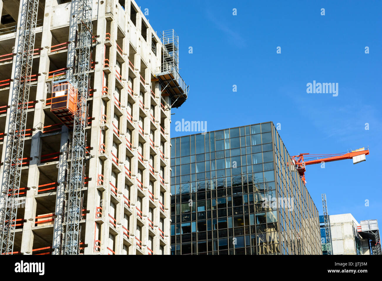Low angle view of a glass building between two concrete buildings under construction with a red tower crane against Stock Photo