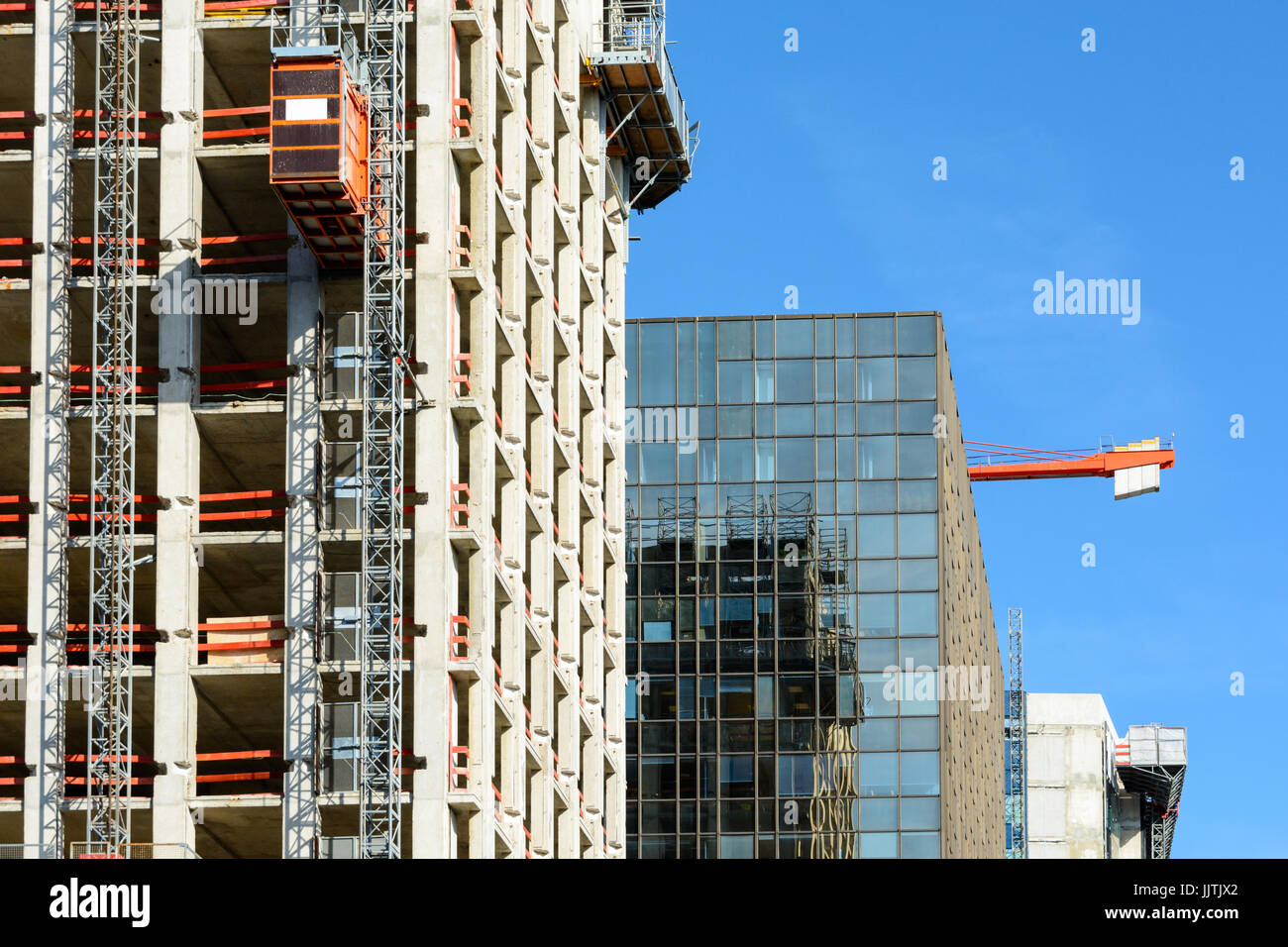 Front view of a glass building between two concrete buildings under construction with a red tower crane against Stock Photo