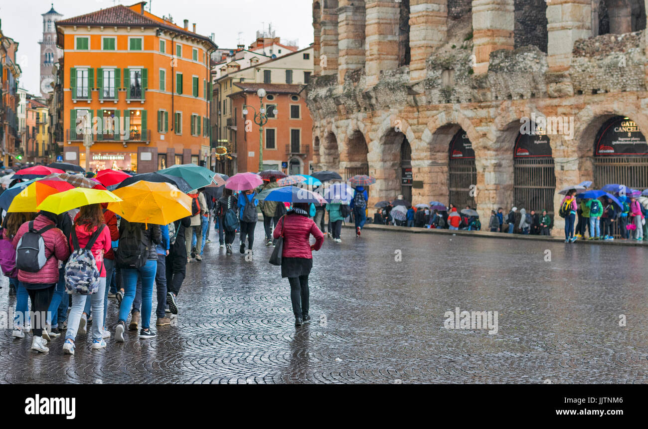 VERONA ITALY A DAY OF RAIN AT THE ARENA A GROUP OF TOURISTS WITH  COLOURED UMBRELLAS - Stock Image
