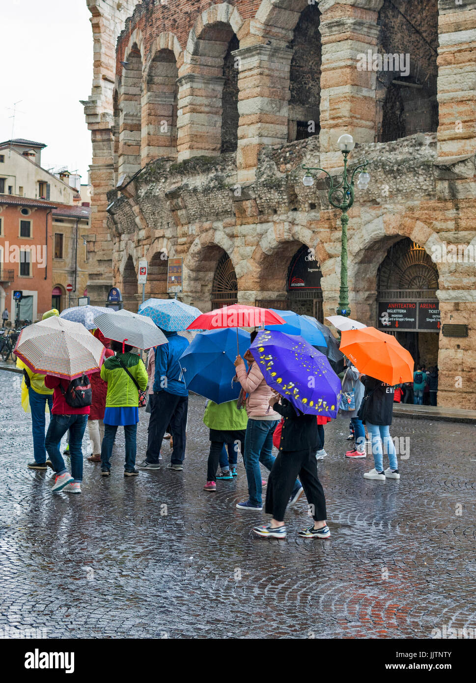 VERONA ITALY THE ARENA ON A RAINY DAY MULTI COLOURED UMBRELLAS ON SHOW - Stock Image