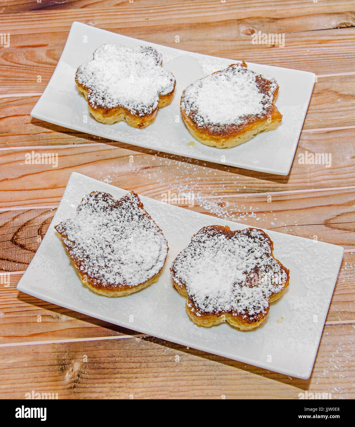 Homemade Creme brulee with powder sugar,  burnt cream, crema catalana, or Trinity cream, white plate and wood background. - Stock Image
