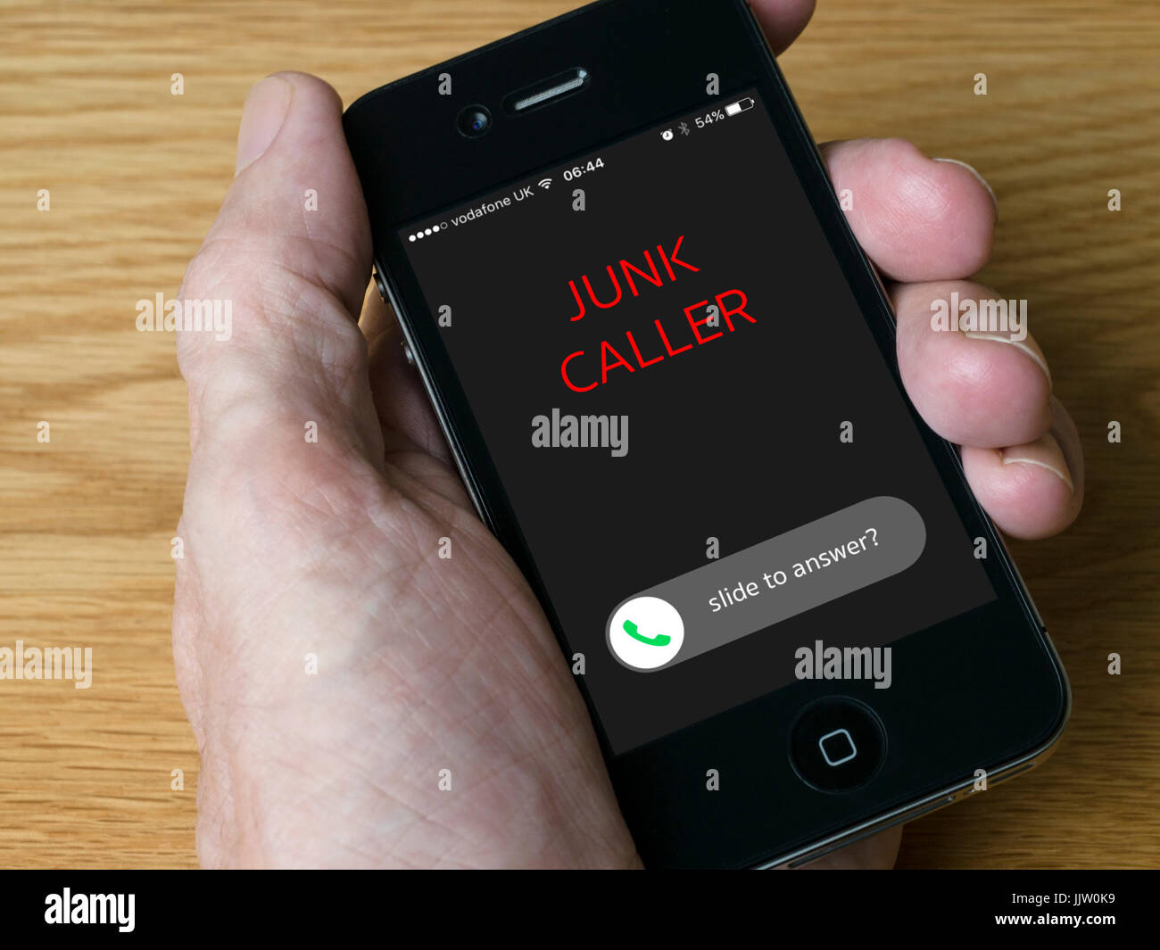 Concept image - Incoming nuisance junk phone call on handheld iPhone mobile phone display - Stock Image