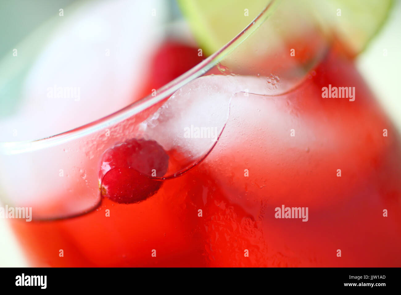 Closeup view of an icy drink made with cranberry juice with fresh berries and a slice of lime - Stock Image