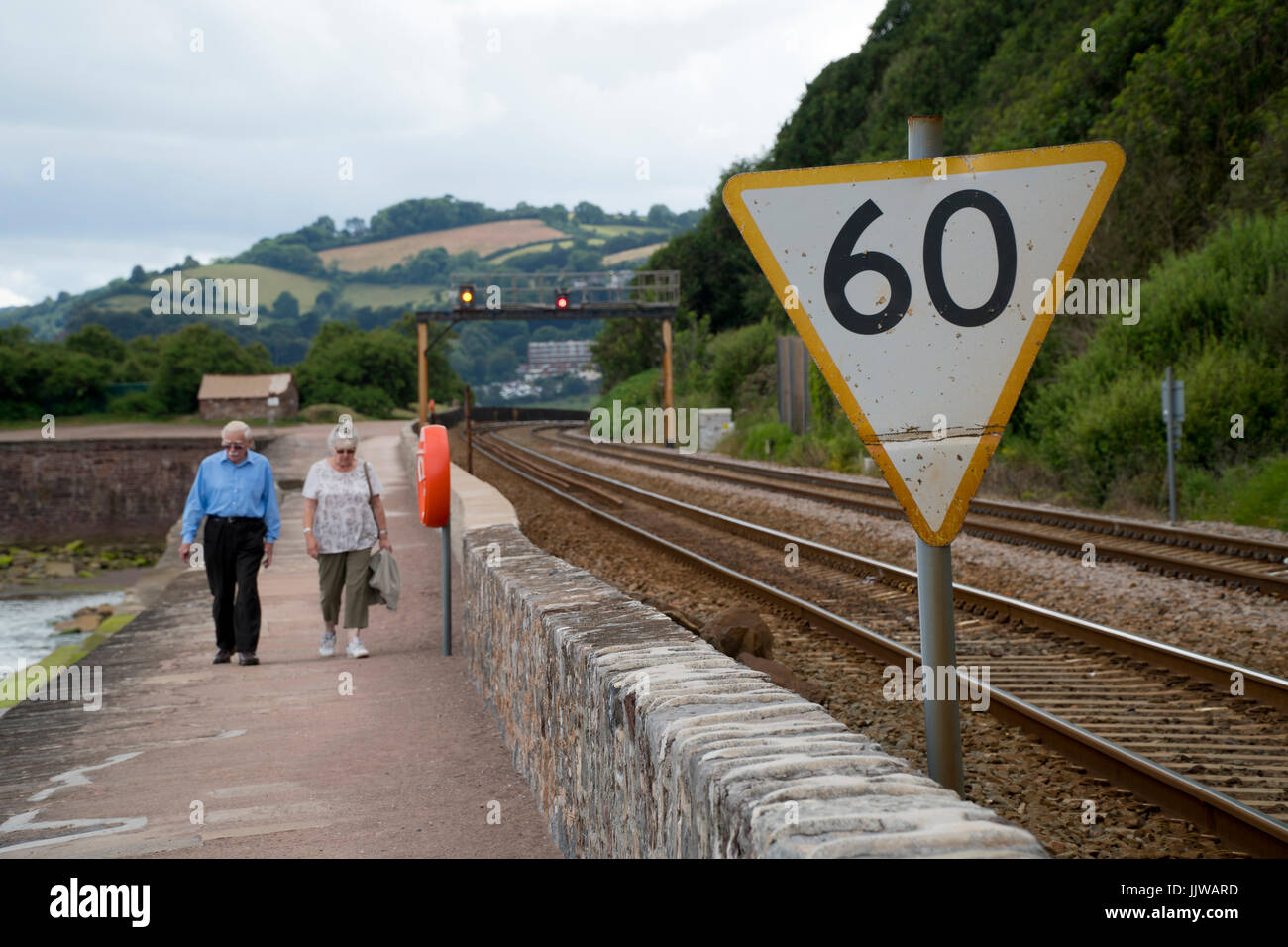 Elderly couple in the distance walking next to a rail line and a 60 mph speed sign for trains in the foreground, - Stock Image