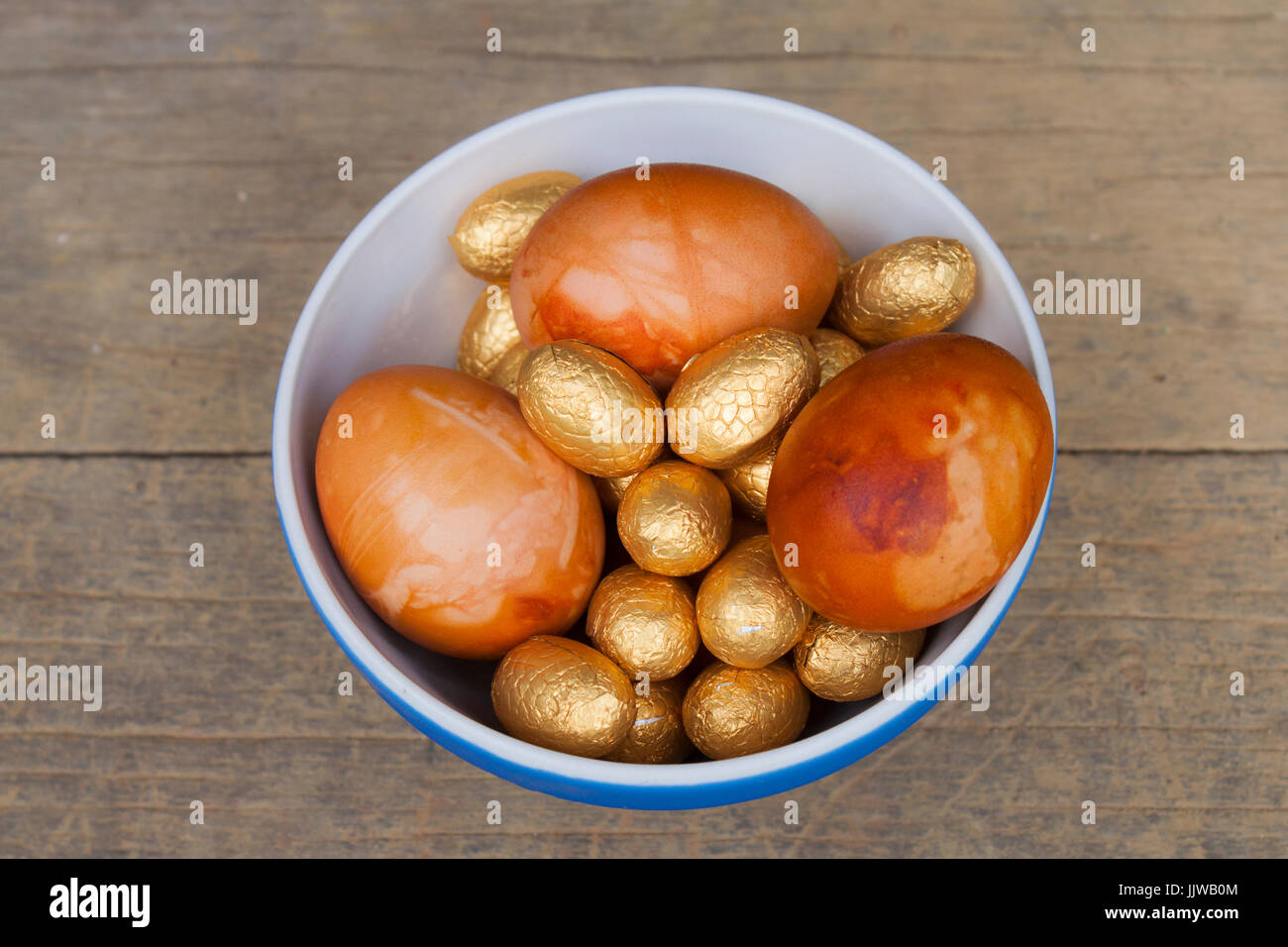 Golden Easter eggs in a bowl. Onions were used to give them an aesthetically pleasing golden look. - Stock Image