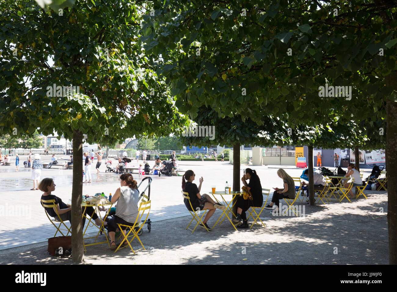Granary Square, King Cross. Londoners enjoy a shady seating area in summer - Stock Image
