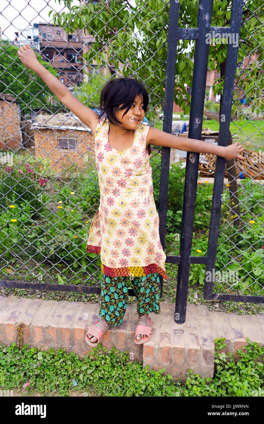 Full length portrait of a young Nepalese girl standing against a chain link fence. - Stock Image