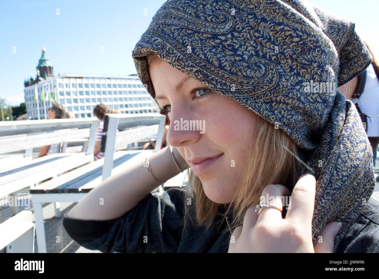 A beautiful young woman putting on her headcloth. - Stock Image