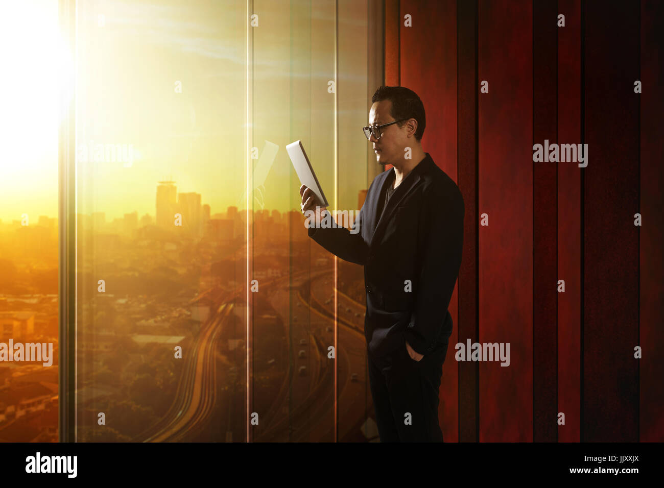 Young asian businessman holding and using digital tablet . Sunrise scene . - Stock Image