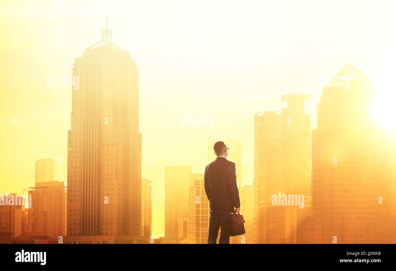 Young smart businessman looking at large city center. Concept of success and appreciation. Standing in front of - Stock Image