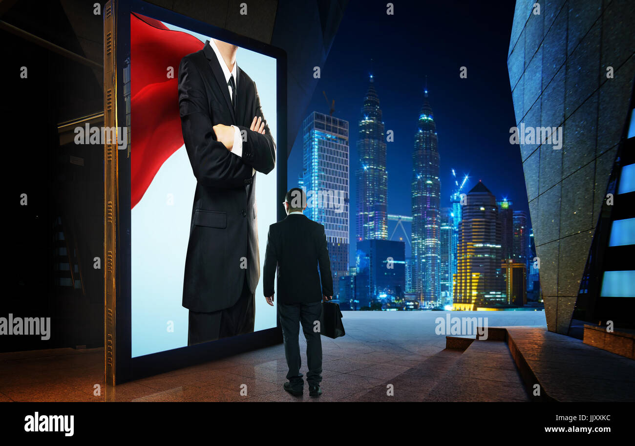 Young businessman looking the hero businessman on the advertising billboard screen . Successful businessman concept - Stock Image