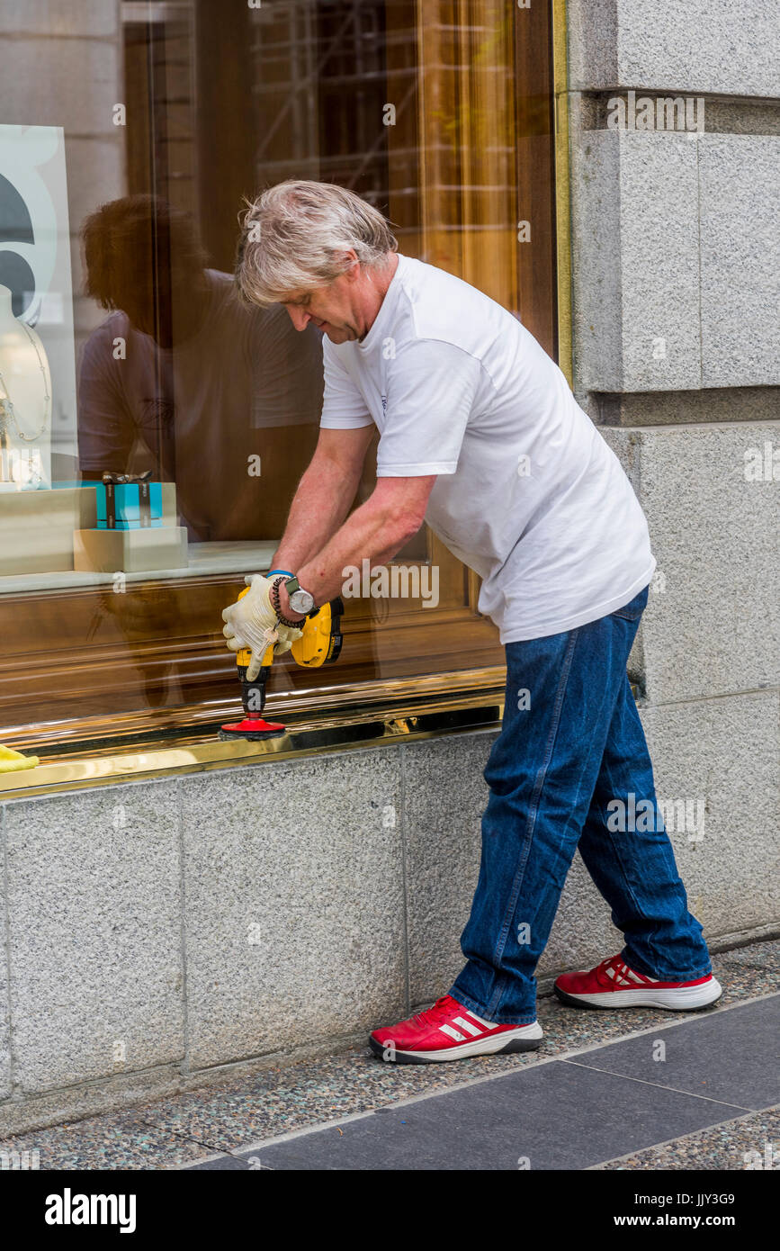 Man polishing brass window frame outside Birk's Jewellers, Vancouver, British Columbia, Canada. - Stock Image