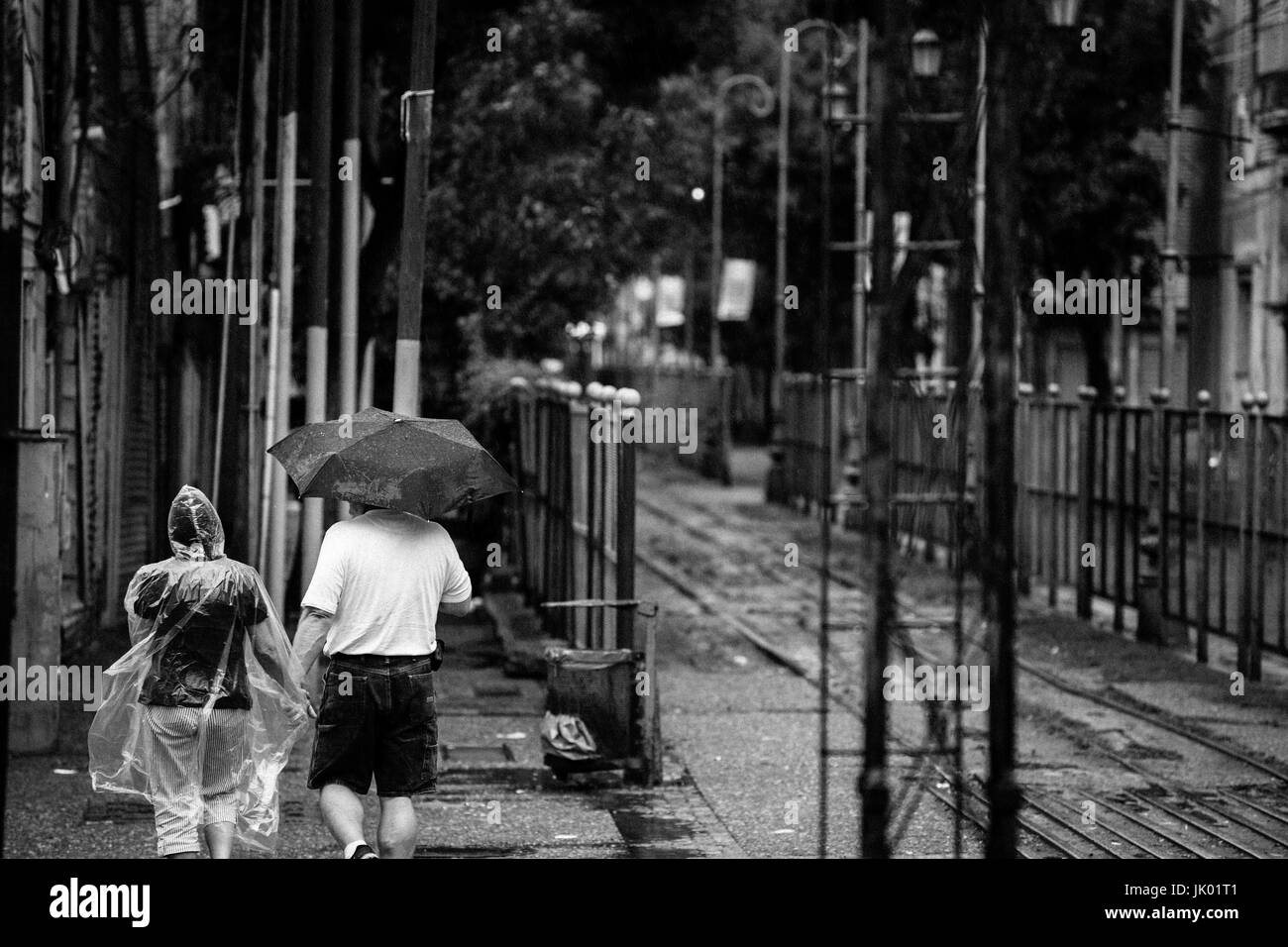 Tourist couple holding hands in the rain, while walking around La Boca, in Buenos Aires, Argentina. - Stock Image