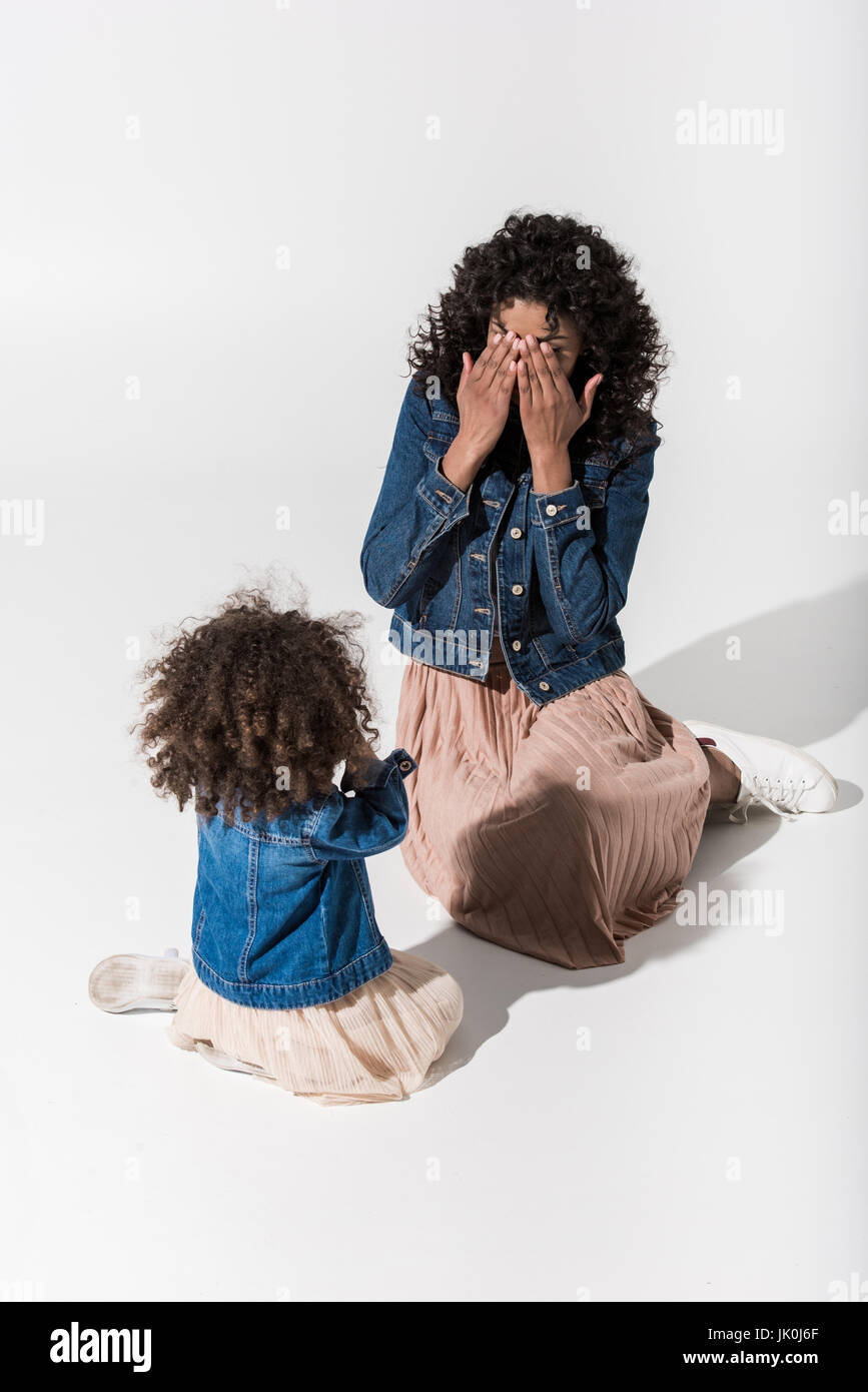 African american mother playing hide-and-seek with her baby girl daughter - Stock Image