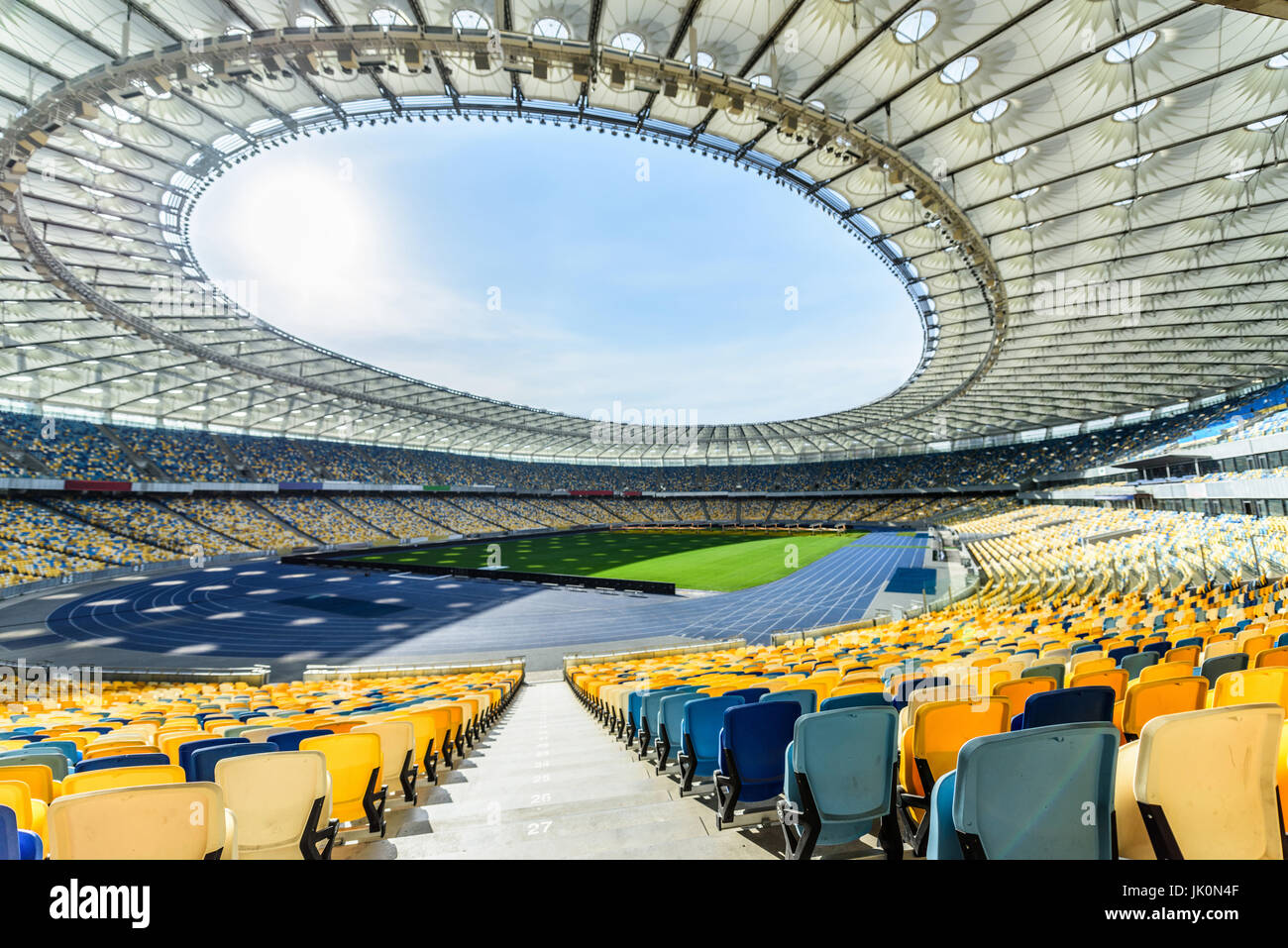 rows of yellow and blue stadium seats on soccer field stadium - Stock Image