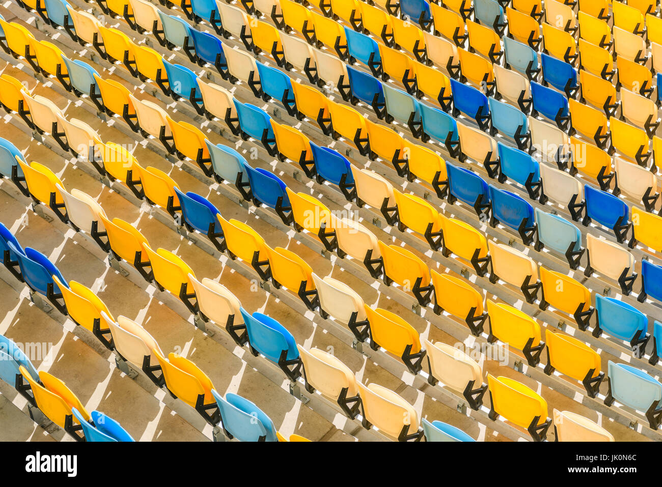 elevated view of rows of yellow and blue stadium seats background - Stock Image