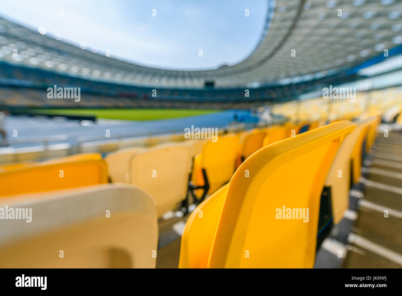 selective focus of yellow stadium seats on football stadium - Stock Image