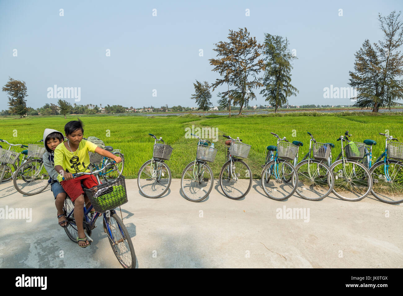 Two boys on one bike speed round the corner by a rice paddy - Hoi An - 13 March 2017 Stock Photo