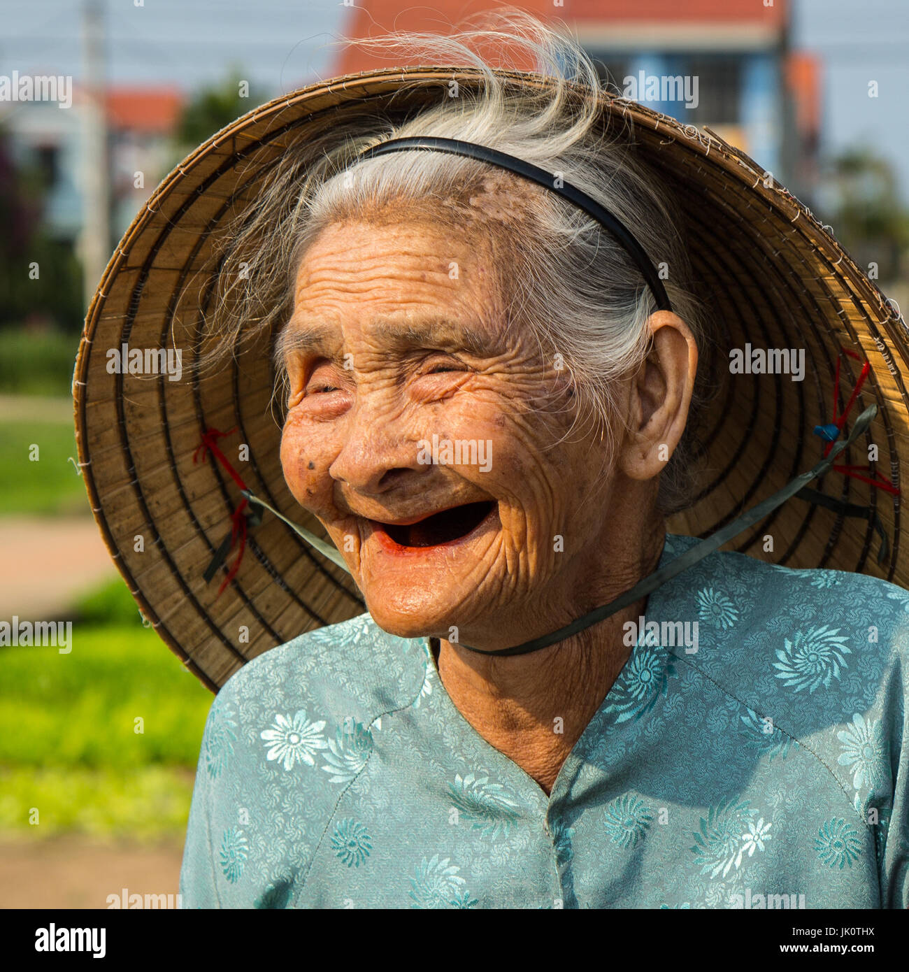 Old Vietnamese lady with a big beautiful smile - Stock Image