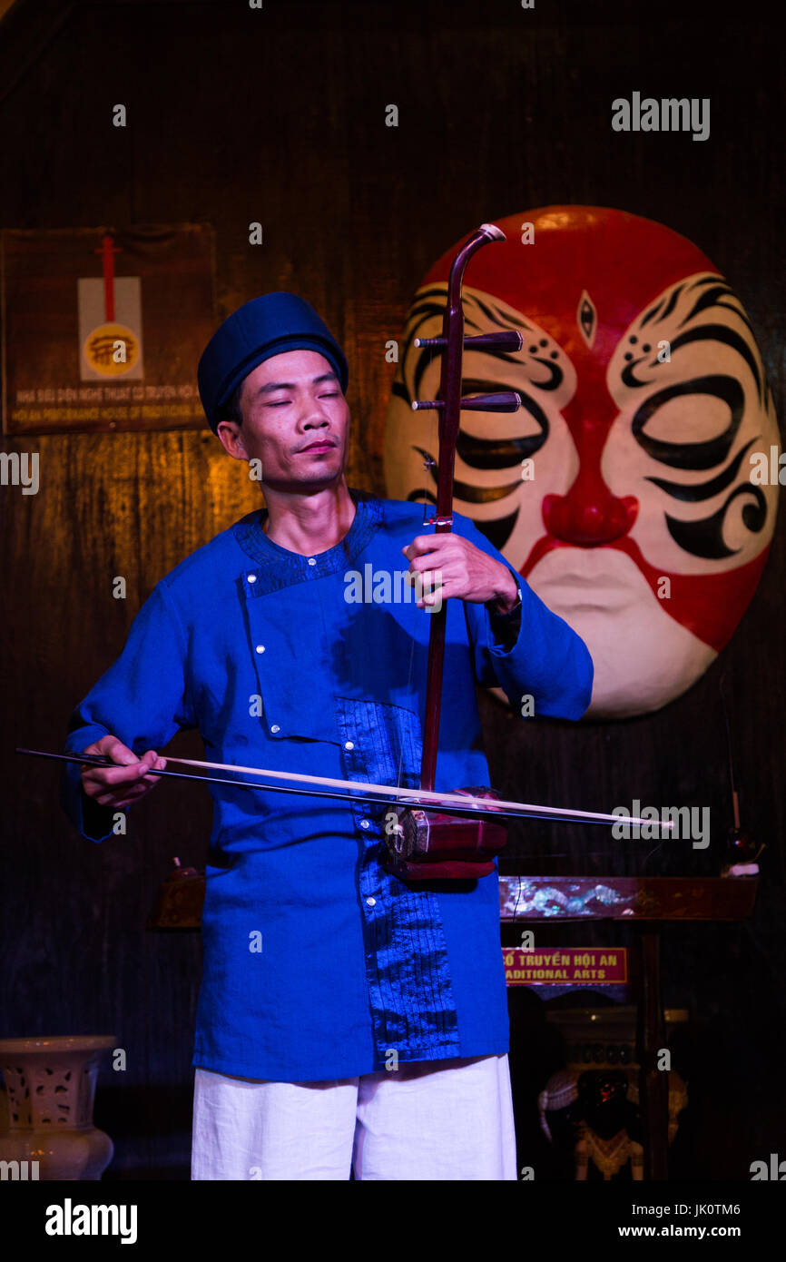 Male musician playing traditional string instrument - Hoi An - 14 March 2017 - Stock Image