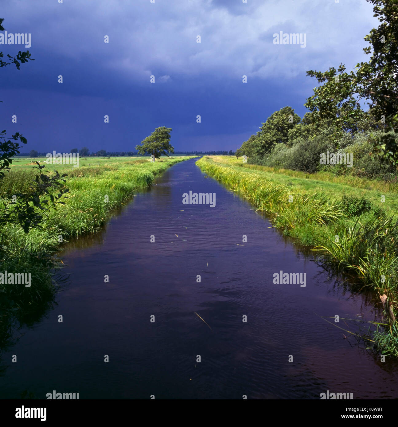 'departing thunderstorm leaves overfull drainage channel in hunteniederung. departing storm and brimful drainage - Stock Image