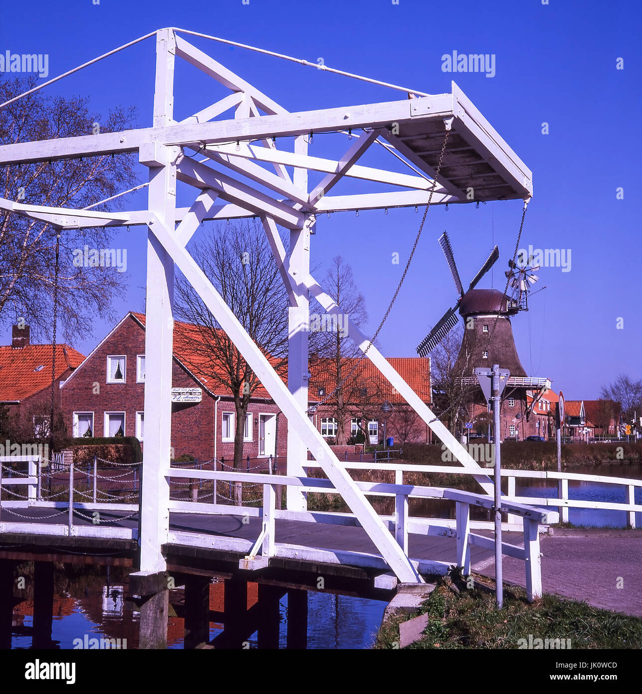 'white balance bridge about the canal from mittegrossefehn, in the background reetgedeckte windmill. white folding - Stock Image