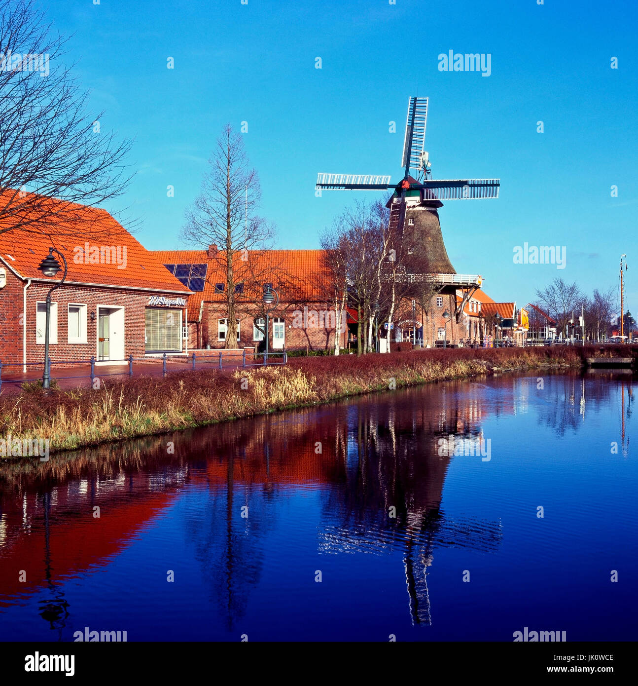'canal by MITTEGROSSEFEHN with windmill in the prespring. canal through MITTEGROSSEFEHN with windmill; early - Stock Image