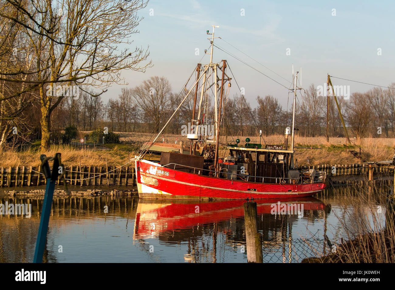 long-served red fishing boat to the eventide in his sleeping place in the vareler harbour, langgedientes rotes fischerboot - Stock Image