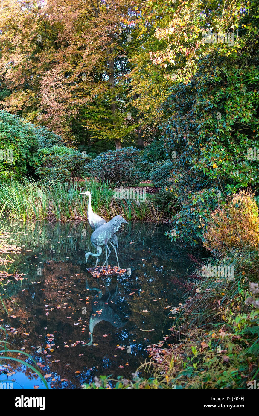 small waters in the autumnal one park with true to life plastic of a heron's pair, kleines gewaesser im herbstlichen - Stock Image