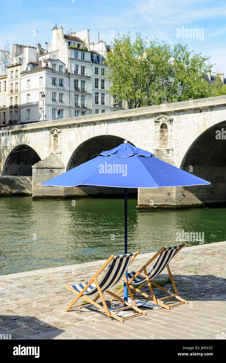 Two blue and white striped deck chairs in the sun under a blue parasol on the bank of the river Seine with typical Stock Photo