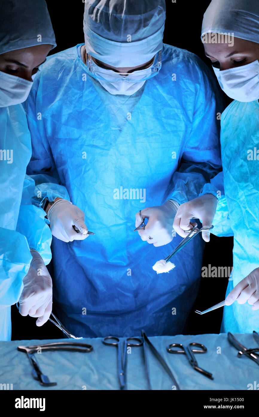 Medical team performing operation. Group of surgeon at work in operating theatre toned in blue. - Stock Image