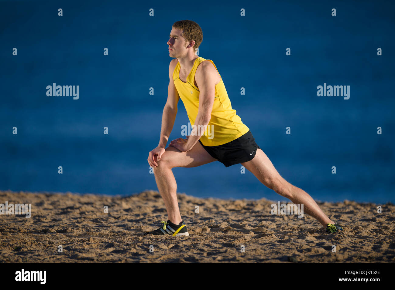 Runner warming up stretching leg muscles - Stock Image