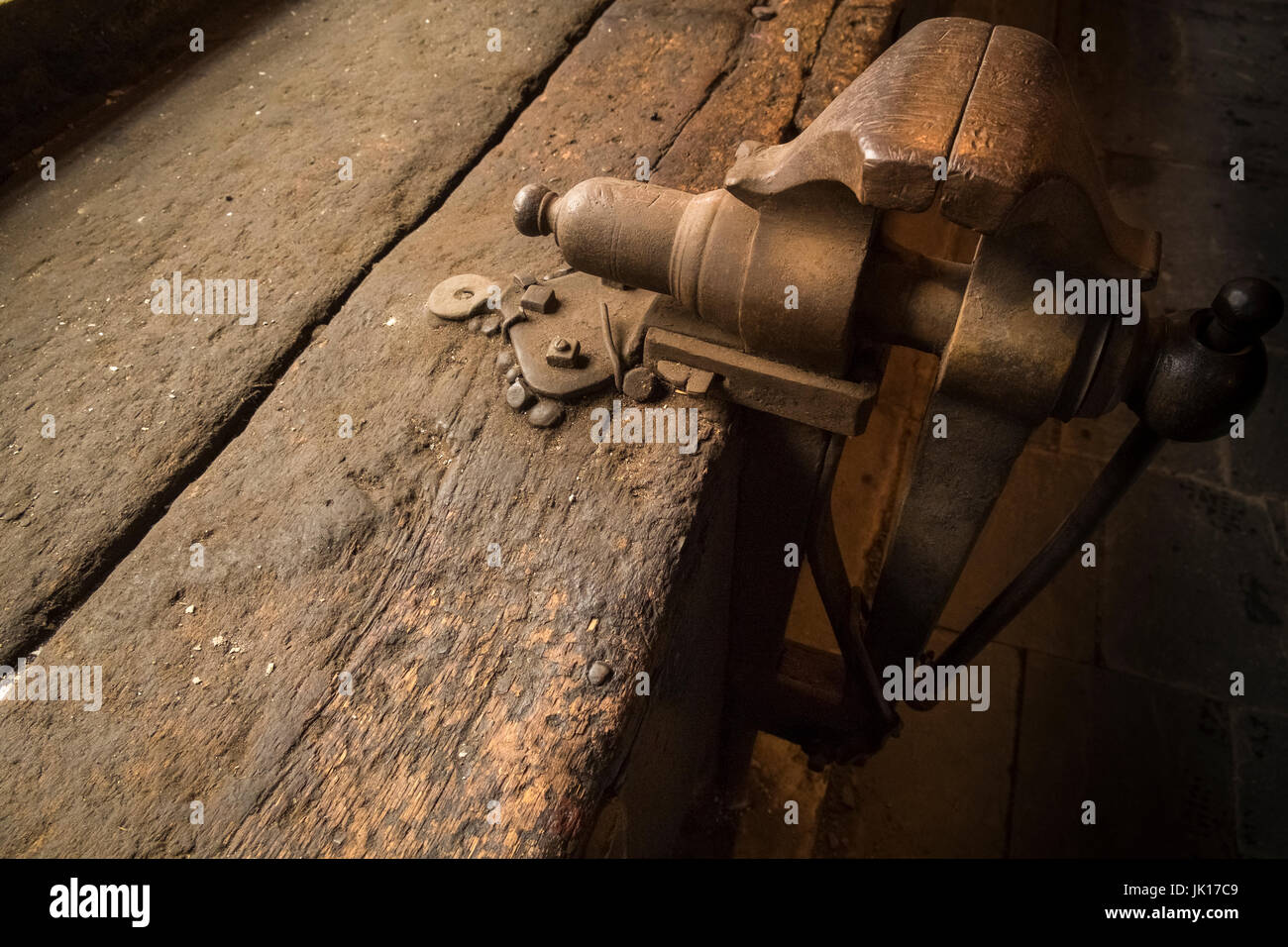 Old metal vice attached to workbench made from worn wooden sleepers. - Stock Image