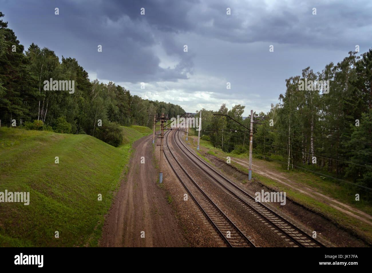 empty railway with dark skies - Stock Image