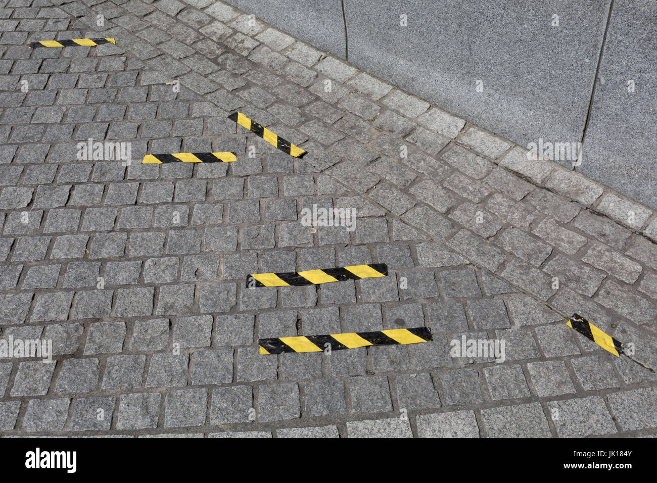 Yellow and black hazard tape on the ground of the pavement in Jubilee Gardens, on 20th July 2017, on the Southbank, - Stock Image