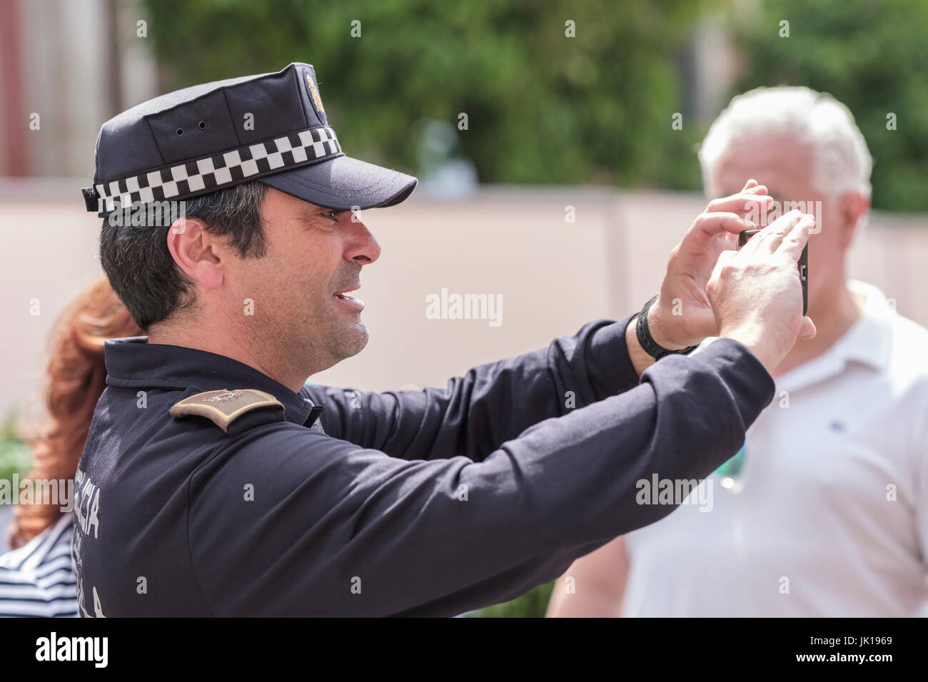 Policeman taking photograph for tourists, Spain, - Stock Image