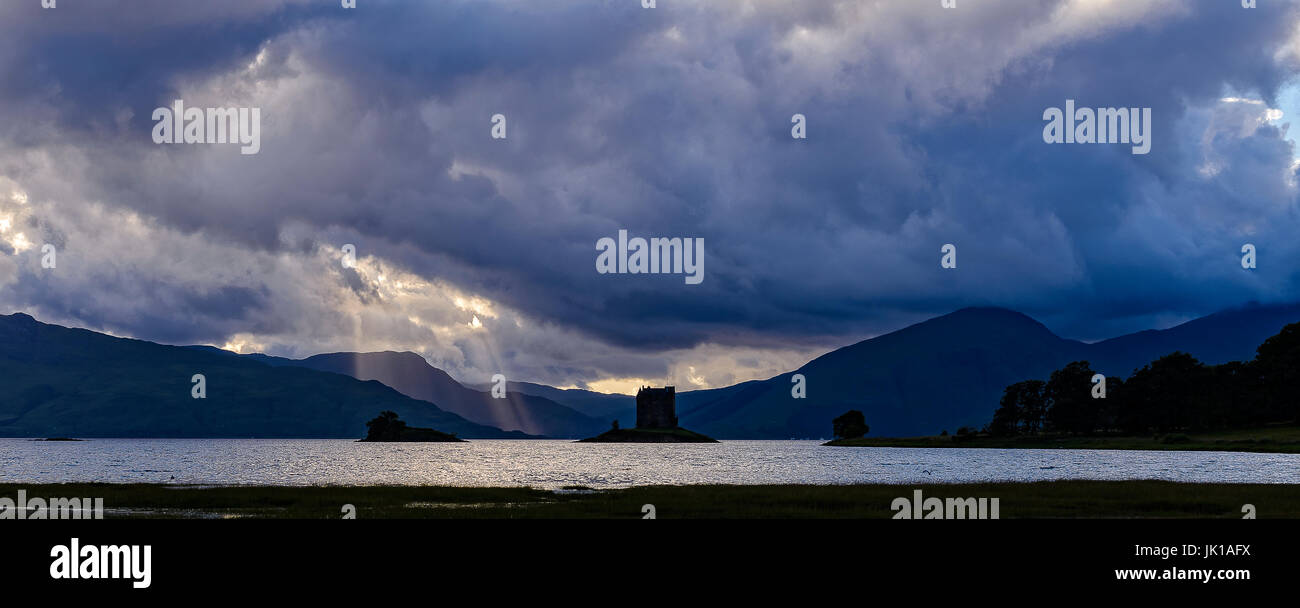 Panoramic view of Castle Stalker silhouetted against the mountains - Stock Image