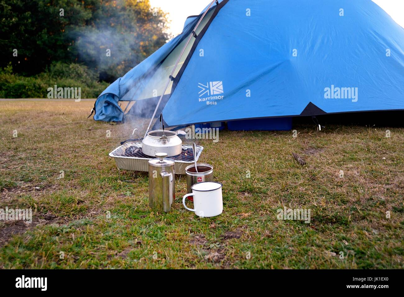 Boiling water on barbeque to make coffee when camping - Stock Image