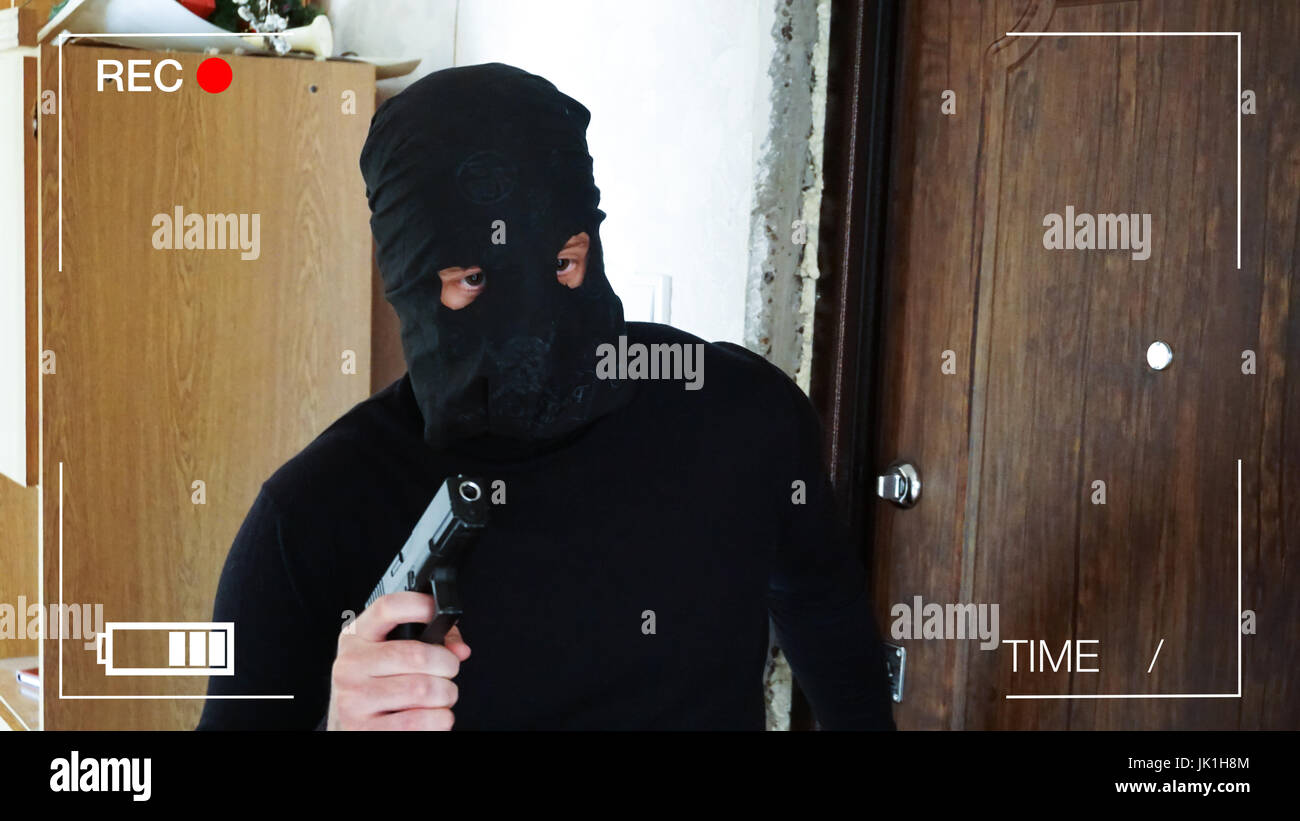 surveillance camera recorded the thief,who broke into the house with a gun. - Stock Image
