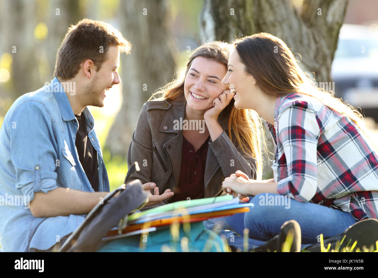 Three happy students talking after classes sitting on the grass outside in a park - Stock Image
