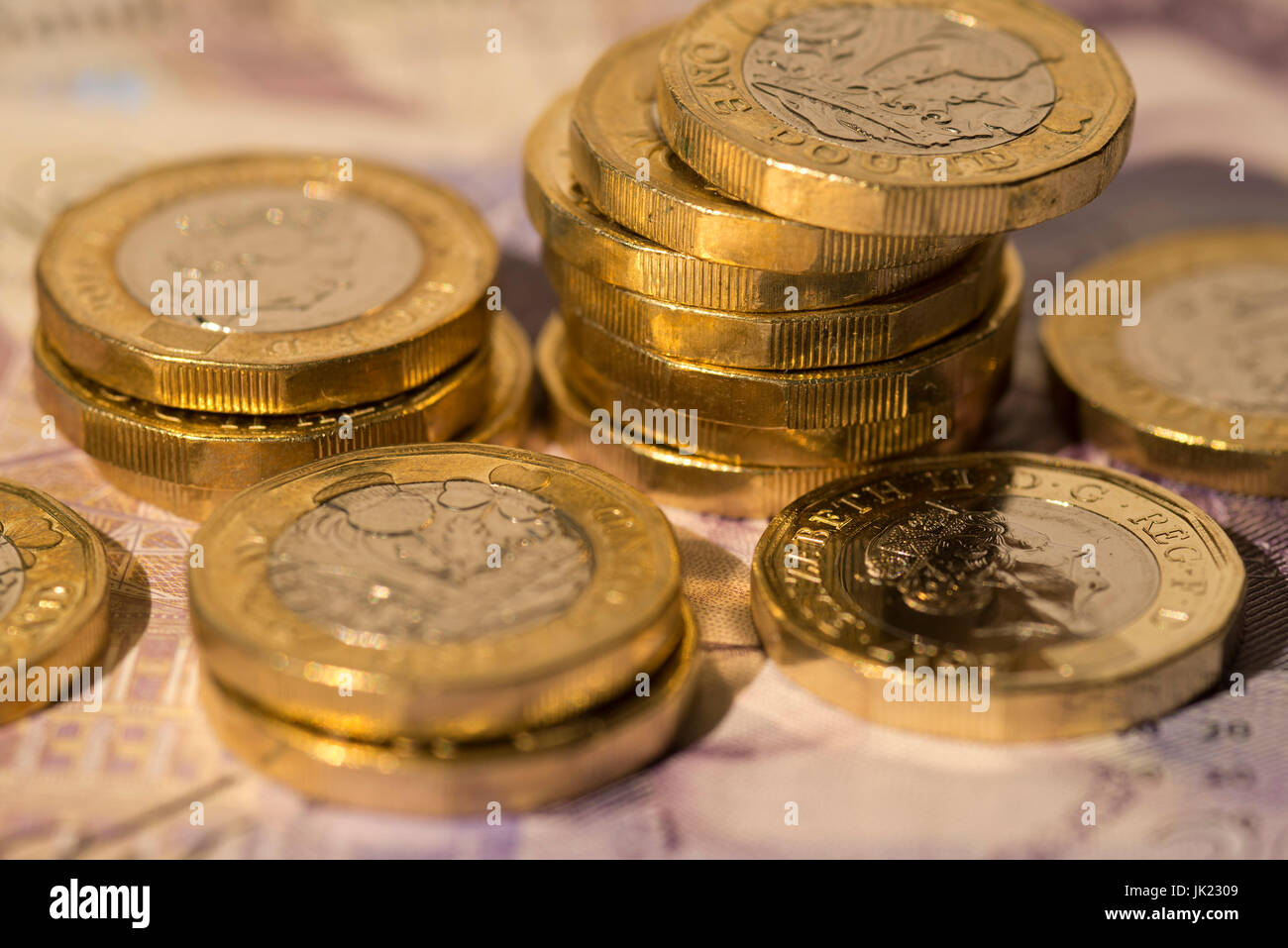 New (2016) British pound (GBP) coins sitting on a 20 pound note. - Stock Image