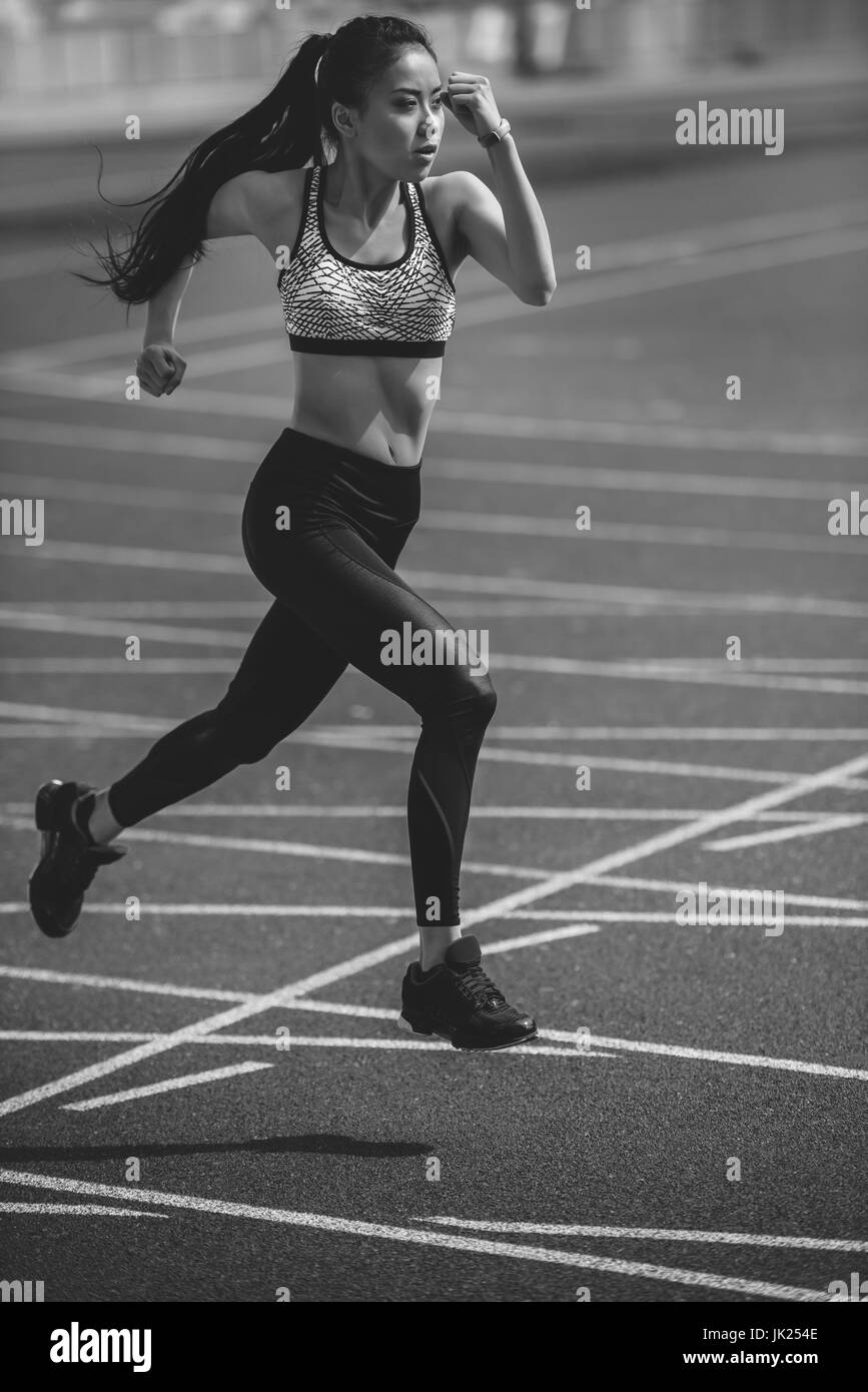 Athletic young sportswoman sprinting on running track stadium, black and white photo - Stock Image