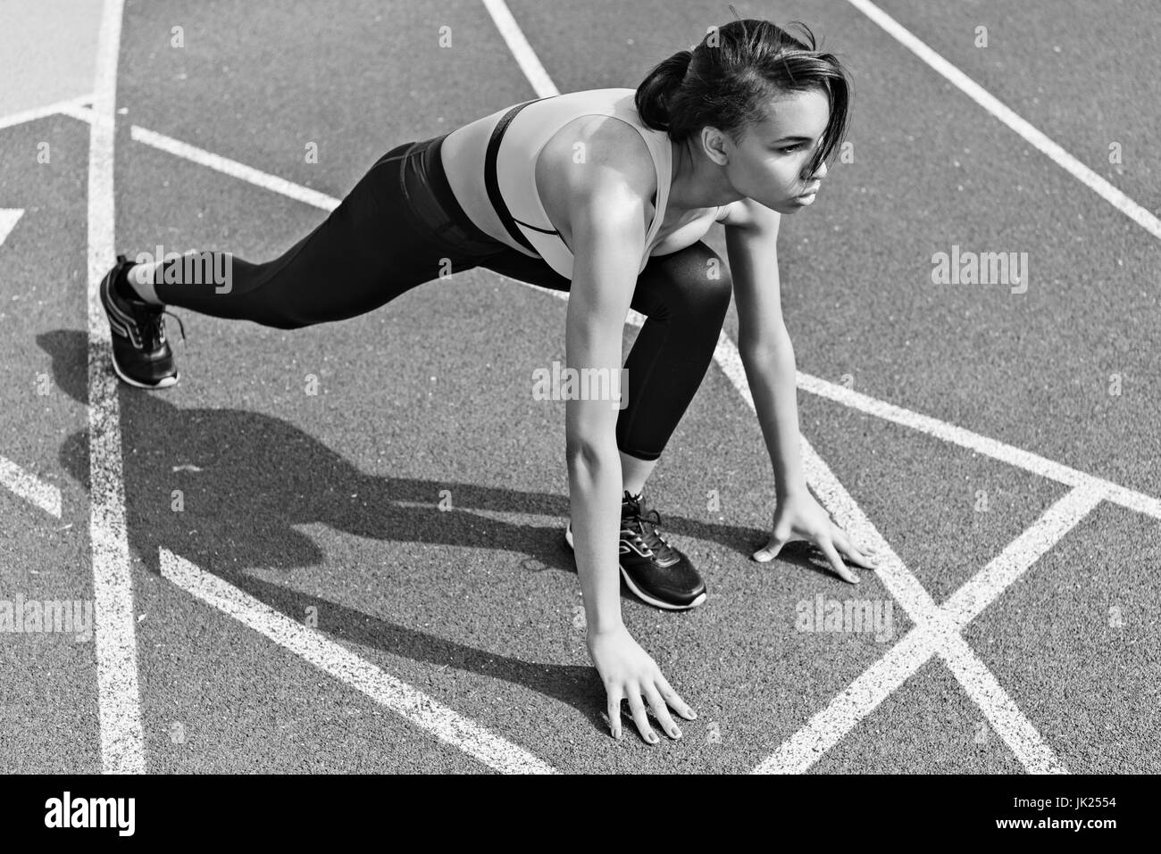 Concentrated athletic young runner on starting line at running track stadium, black and white photo - Stock Image