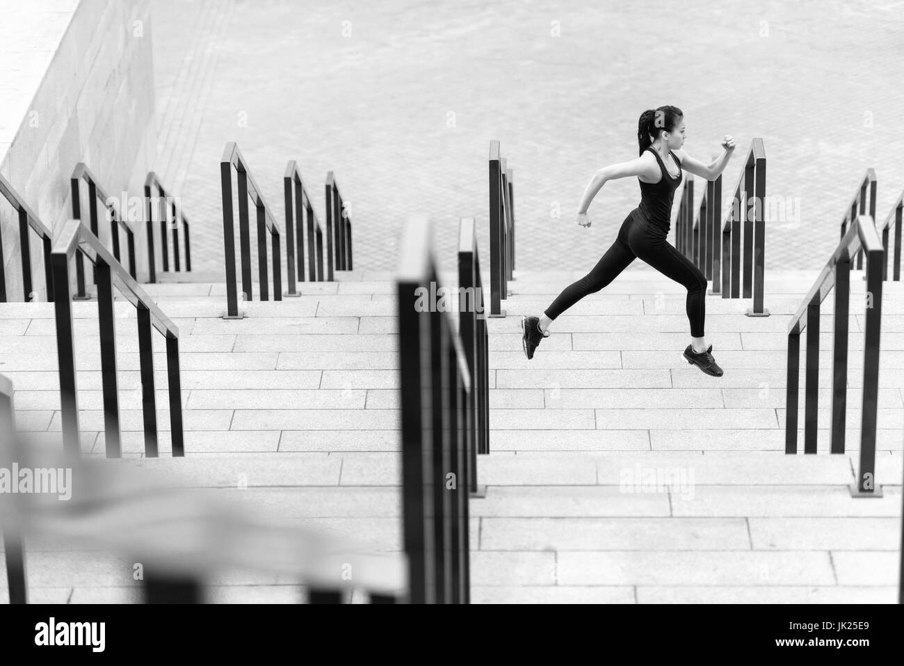 Side view of athletic young woman in sportswear running on stadium stairs, black and white photo - Stock Image