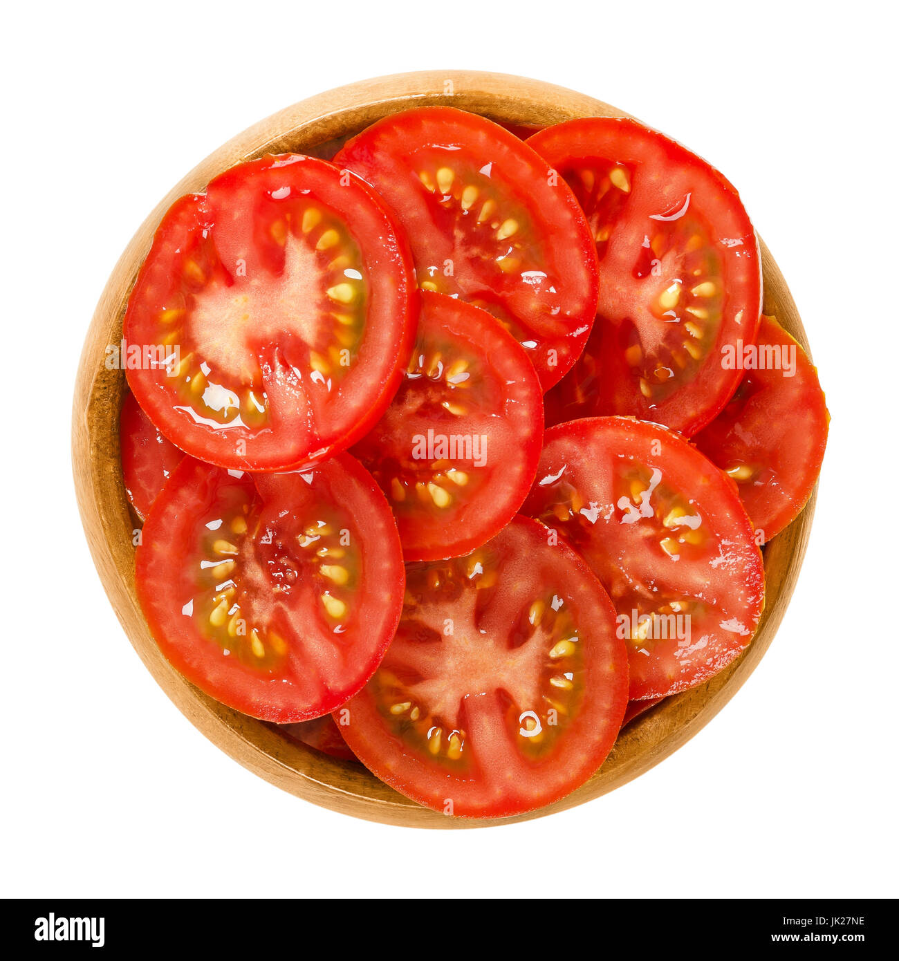 Tomato slices in wooden bowl. Edible ripe and raw fruit of Solanum lycopersicum with red color, cut into thin slivers. - Stock Image