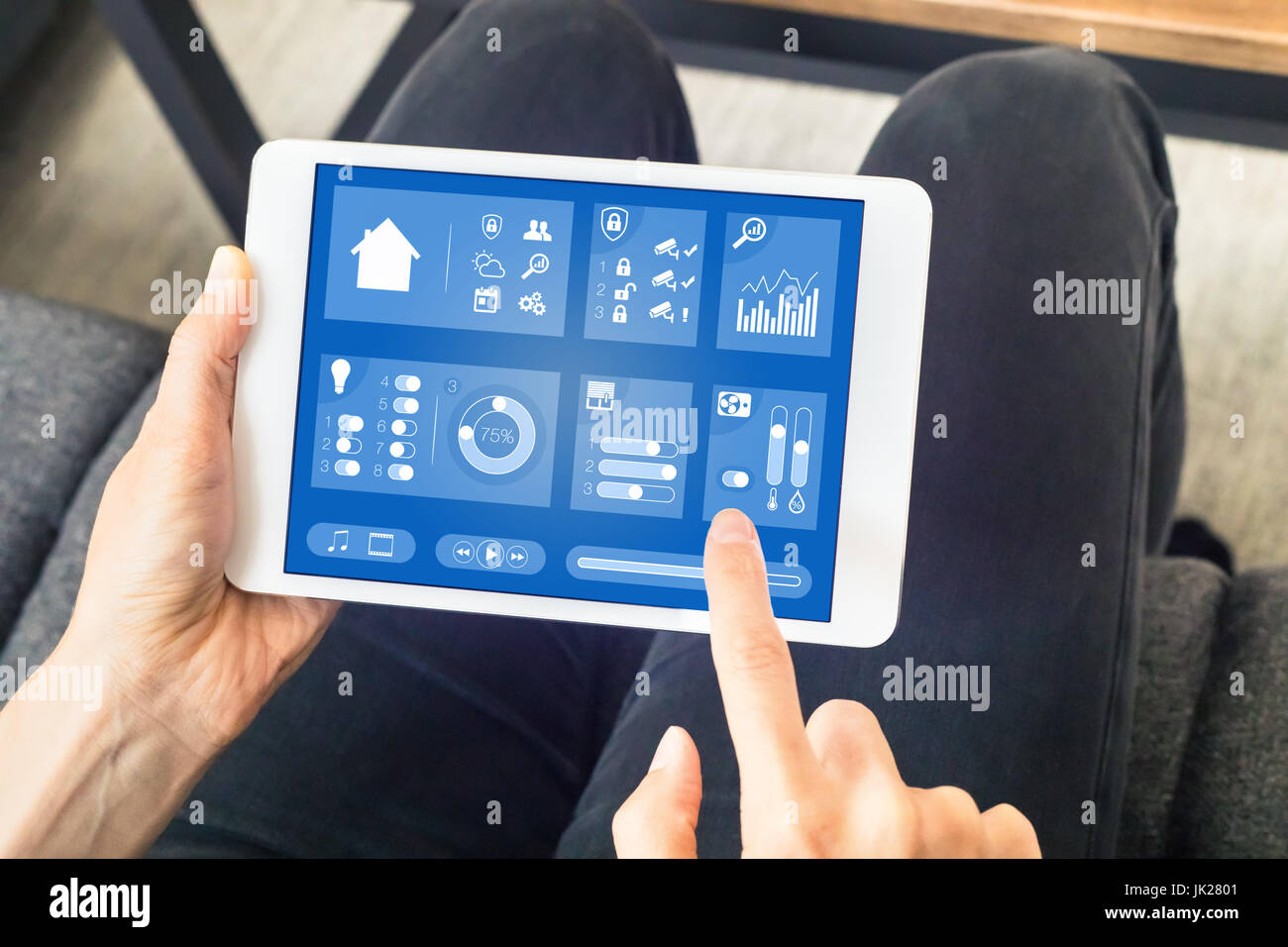 Person using smart home automation dashboard on a digital tablet computer with internet of things (IOT) to control - Stock Image