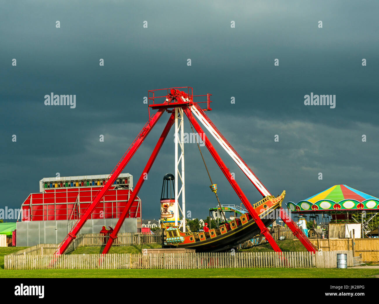 Southport Funfair against a black sky and lit by the sun, Lancashire - Stock Image