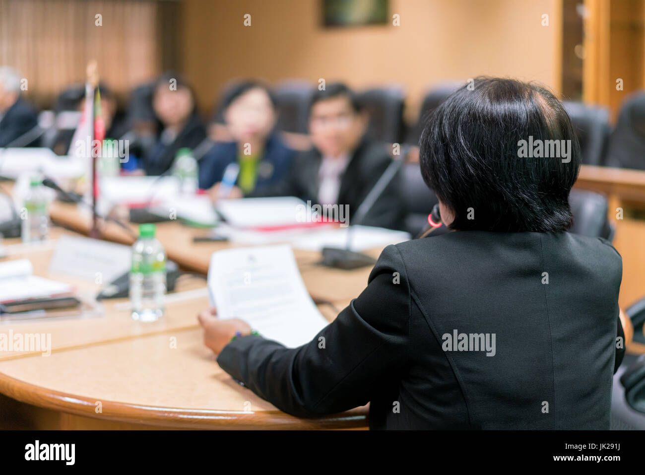 Businesswoman speaker with microphone making presentation at business conference. Business people meeting conference - Stock Image